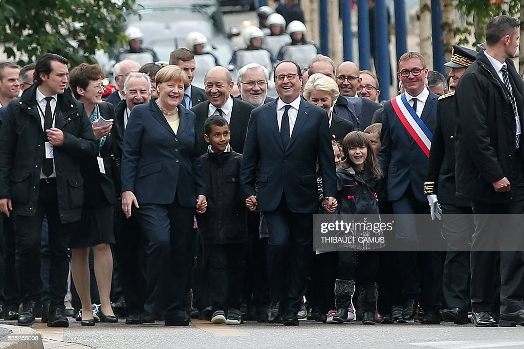 TOPSHOT - France's President Francois Hollande (C) and German Chancellor Angela Merkel (3rd L) smile and hold hands of children as they arrive for a remembrance ceremony to mark the centenary of the battle of Verdun, in Verdun, on May 29, 2016. The battle of Verdun, in 1916, was one of the bloodiest episodes of World War I. The offensive which lasted 300 days claimed more than 300,000 lives. / AFP / POOL / Thibault Camus