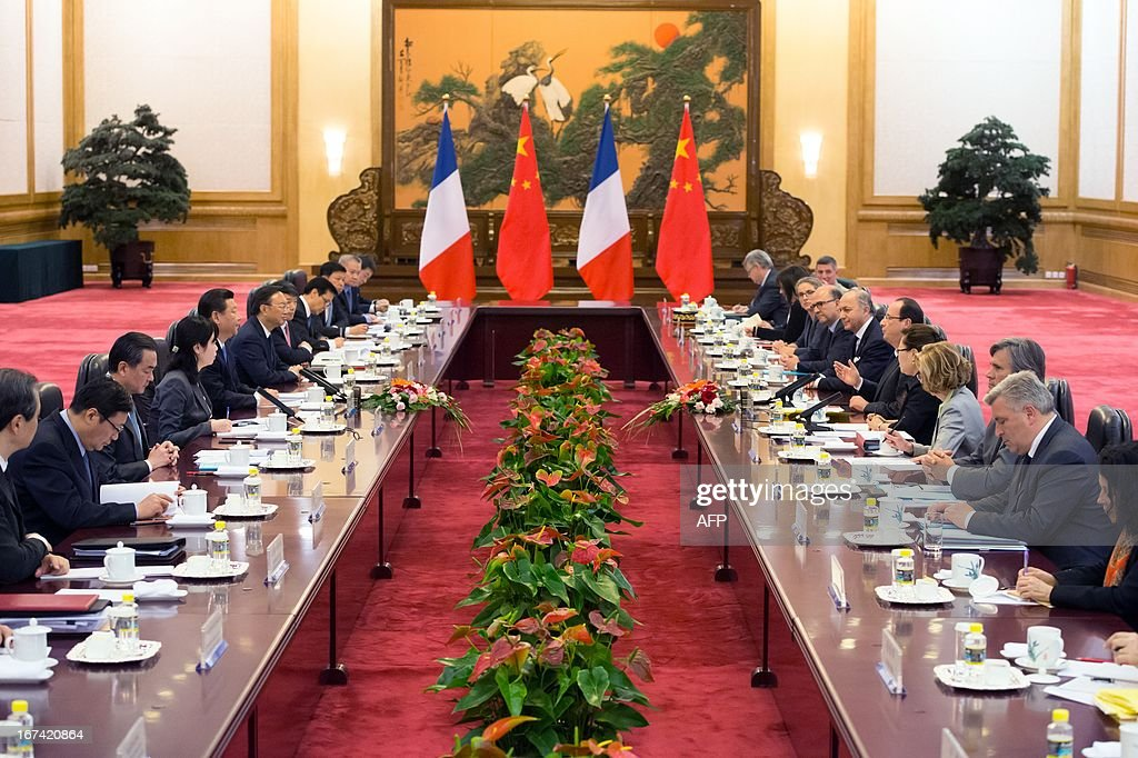 France's President Francois Hollande (6th R) and his Chinese counterpart Xi Jinping (5th L) take part in a meeting with ministers as part of a two-day visit of State at the Great Hall of the People in Beijing on April 25, 2013.