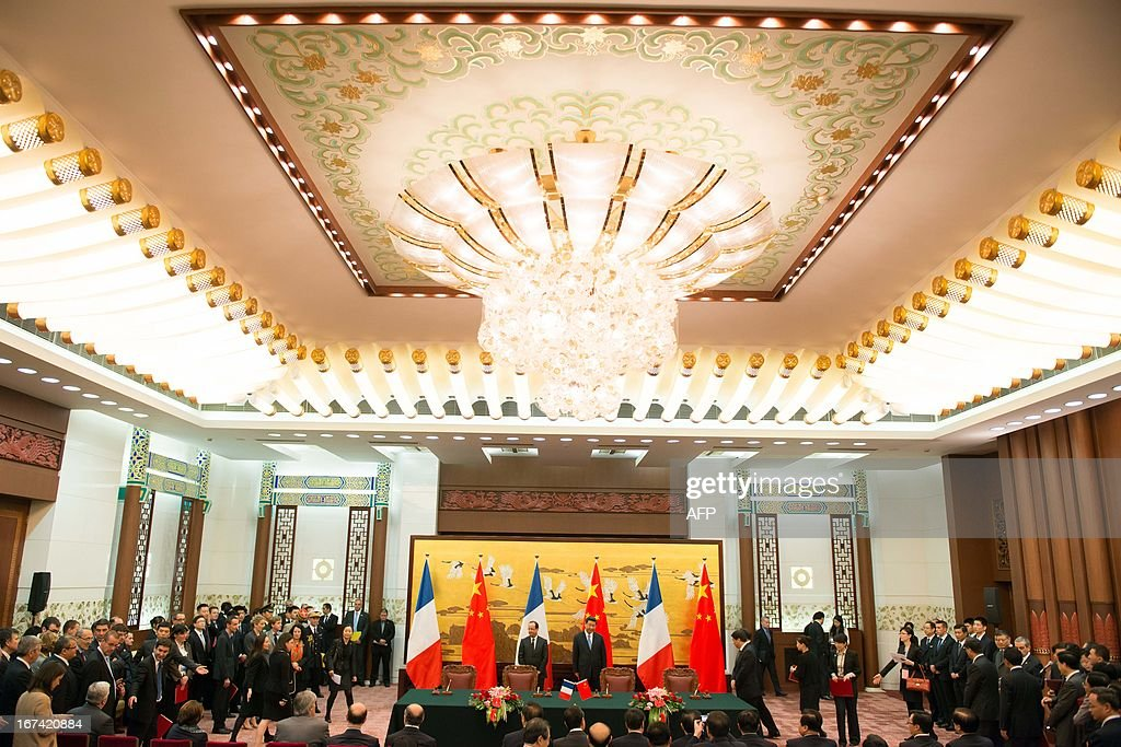 France's President Francois Hollande (C,L) and his Chinese counterpart Xi Jinping (C,R) take part in a signing contracts ceremony as part of a two-day visit of State at the Great Hall of the People in Beijing on April 25, 2013.