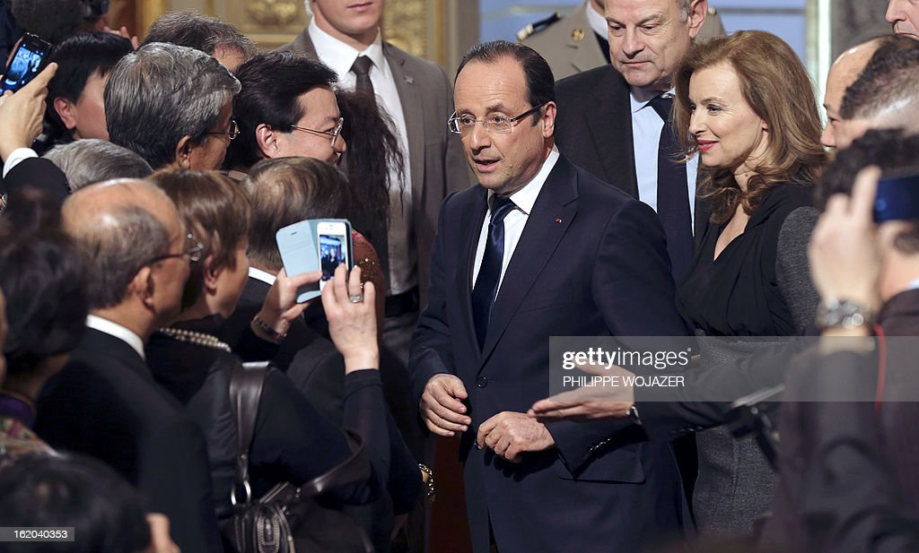 France's President Francois Hollande (C) and his companion Valerie Trierweiler speak to guests during a ceremony with representatives of France's Chinese community associations on February 18, 2013 at the Elysee Presidential Palace in Paris, to mark the Chinese Lunar New Year. AFP PHOTO / POOL / PHILIPPE WOJAZER