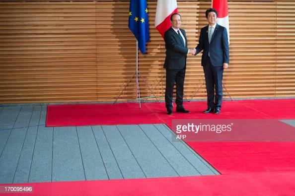 France's President Francois Hollande and Japanese Prime Minister Shinzo Abe shake hands before attending a meeting at the prime ministers official...