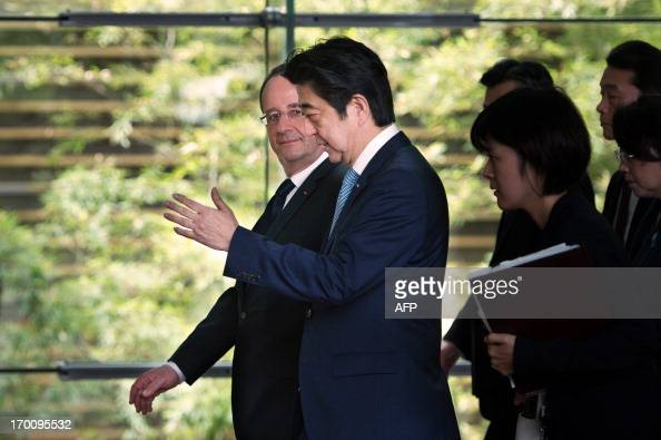 France's President Francois Hollande and Japanese Prime Minister Shinzo Abe arrive to attend a meeting at the prime ministers official residence in...