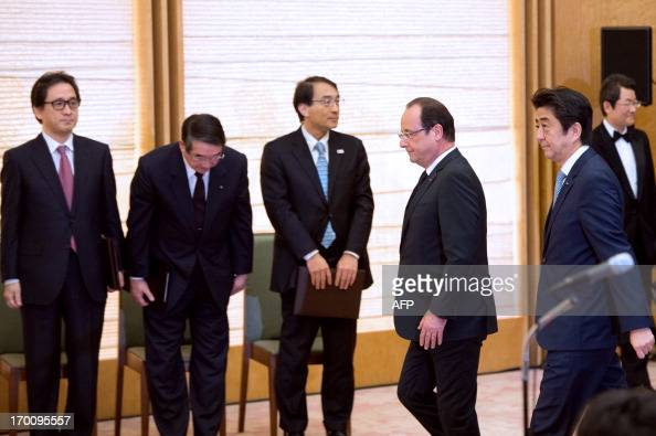 France's President Francois Hollande and Japanese Prime Minister Shinzo Abe arrive to attend a press conference following their meeting at the prime...