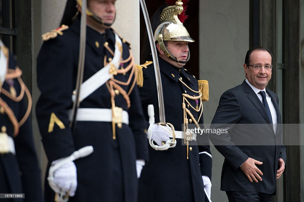 France's President Francois Hollande awaits Prince Albert II of Monaco before their lunch at the Elysee presidential palace in Paris on December 7, 2012.