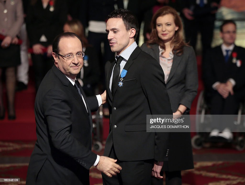 France's President Francois Hollande (L) awards French athlete Antoine Laneyrie (C), bronze medalist at the 2012 London Paralympic Games, as his companion Valerie Trierweiler (R) looks on during a ceremony at the Elysee presidential Palace on February 22, 2013 in Paris. AFP PHOTO / POOL / JACQUES DEMARTHON