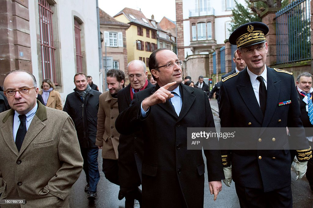 France's President Francois Hollande (C), beside Bas-Rhin prefect Stephane Bouillon (R) and French Junior Minister for European Affairs Bernard Cazeneuve (L), walks through the streets of the eastern French city of Strasbourg on February 5, 2013. Hollande said today that he was ready to compromise on the EU's trillion-euro 2014-20 budget but warned that the spending cuts some members want must not undercut fragile growth.