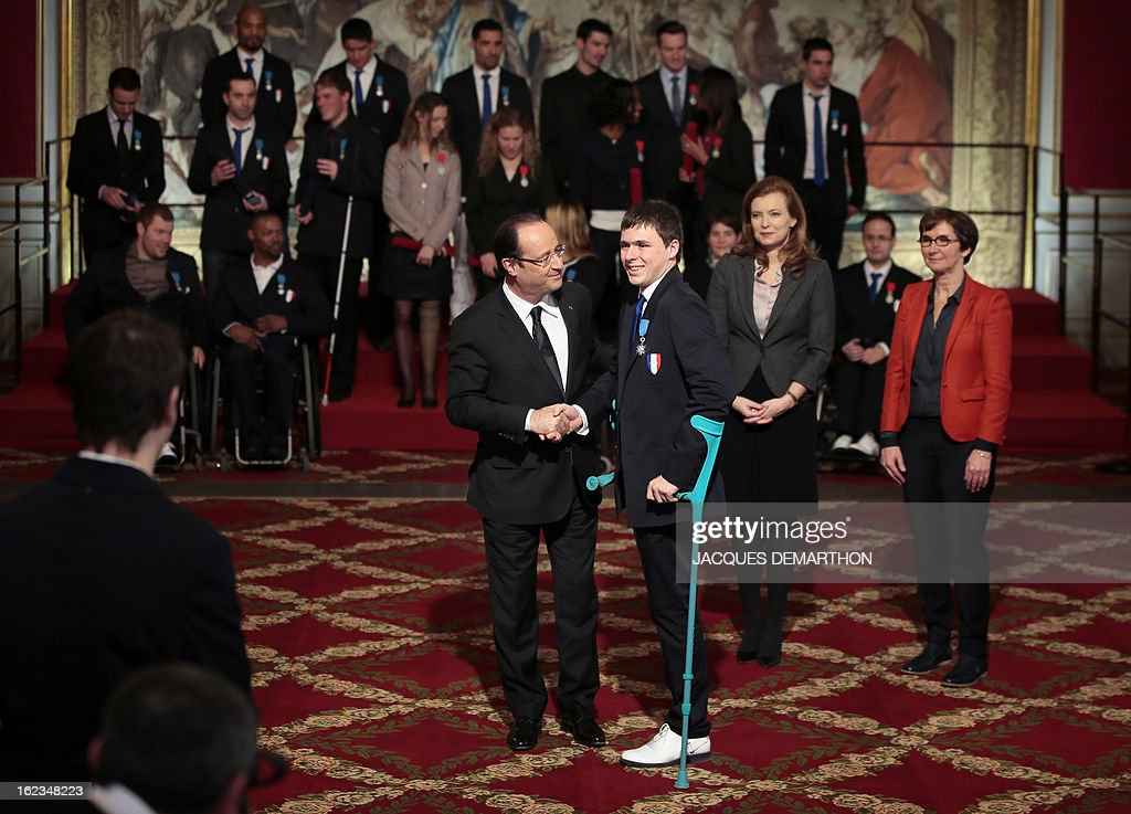 France's President Francois Hollande (L) congratulates French fencer Ludovic Lemoine, silver medalist at the 2012 London Paralympic Games, after awarding him in the Order of Merit, as his companion Valerie Trierweiler (2ndR) looks on during an awarding ceremony at the Elysee presidential Palace on February 22, 2013 in Paris.