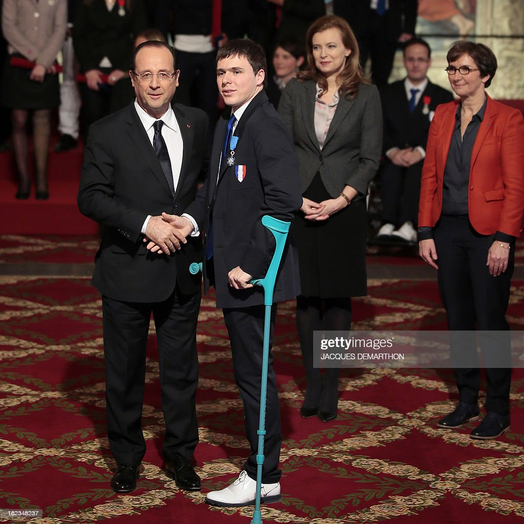 France's President Francois Hollande (L) congratulates French fencer Ludovic Lemoine, silver medalist at the 2012 London Paralympic Games, after awarding him in the Order of Merit, as his companion Valerie Trierweiler (2ndR) and Sports Minister Valerie Fourneyron look on during an awarding ceremony at the Elysee presidential Palace on February 22, 2013 in Paris. AFP PHOTO / POOL / JACQUES DEMARTHON