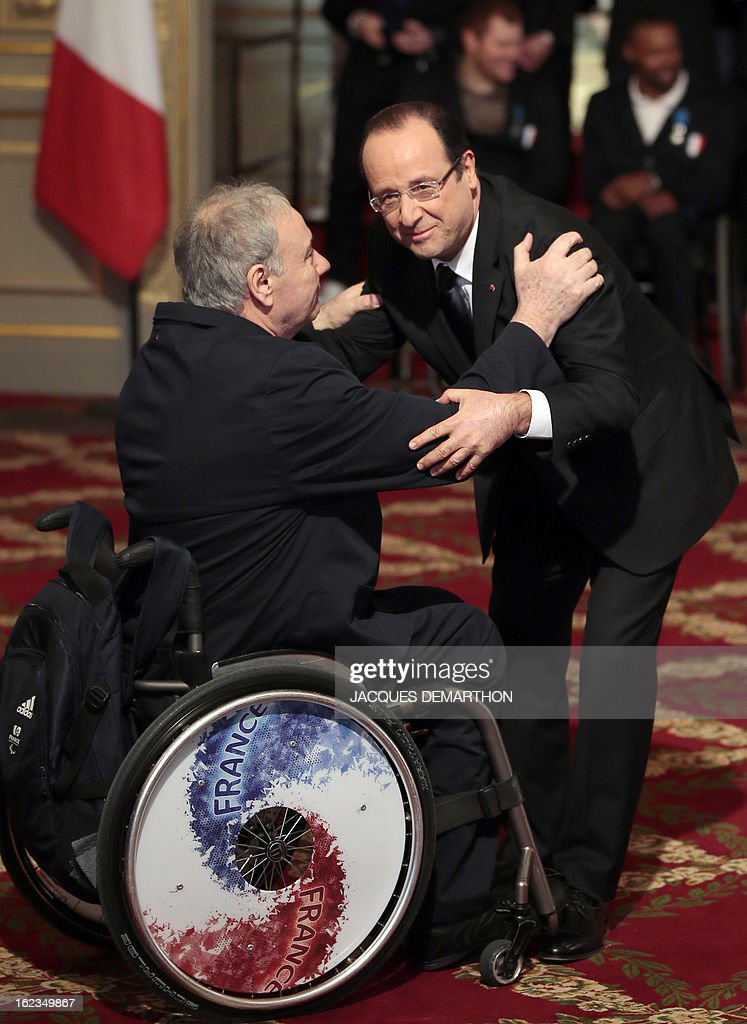 France's President Francois Hollande (R) congratulates General Secretary of the French Paralympic sports Committee, Jean-Paul Moreau after awarding him Knight in the Order of Merit during a ceremony for the 2012 London Paralympic Games athletes at the Elysee presidential Palace on February 22, 2013 in Paris. AFP PHOTO / POOL / JACQUES DEMARTHON