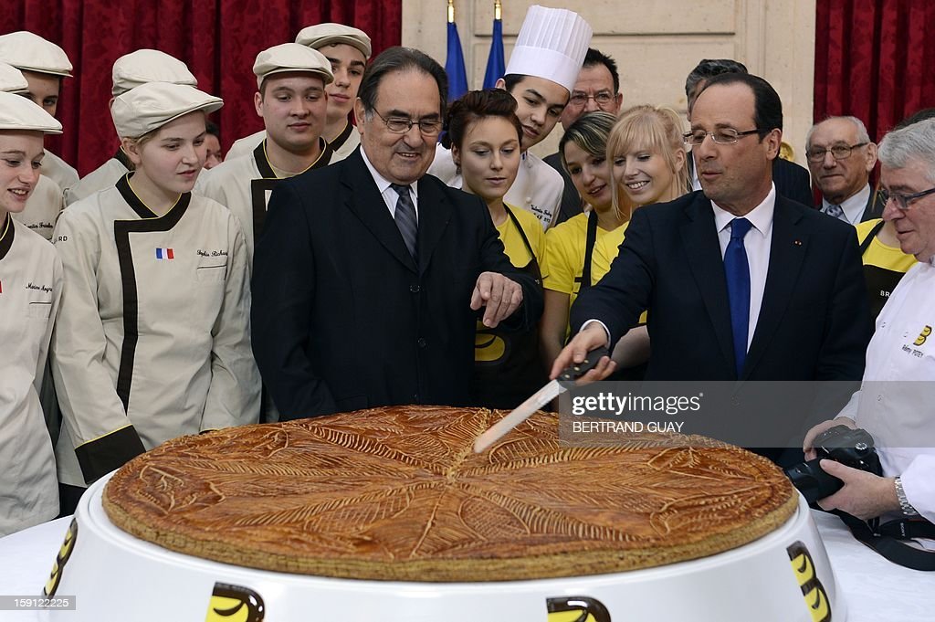France's President Francois Hollande (2nd R) cuts a giant traditional Epiphany cake (galette des rois) next to the president of French bakeries National Confederation Jean-Pierre Crouzet on January 8, 2013 at the Elysee presidential palace in Paris.