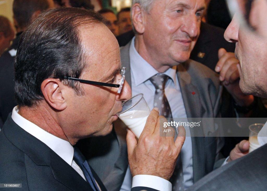 France's President Francois Hollande drinks milk as he attends the International breeding fair (Space) on September 11, 2012 in Rennes, western France. (C) former FNSEA farm union president Jean-Michel Lemetayer.