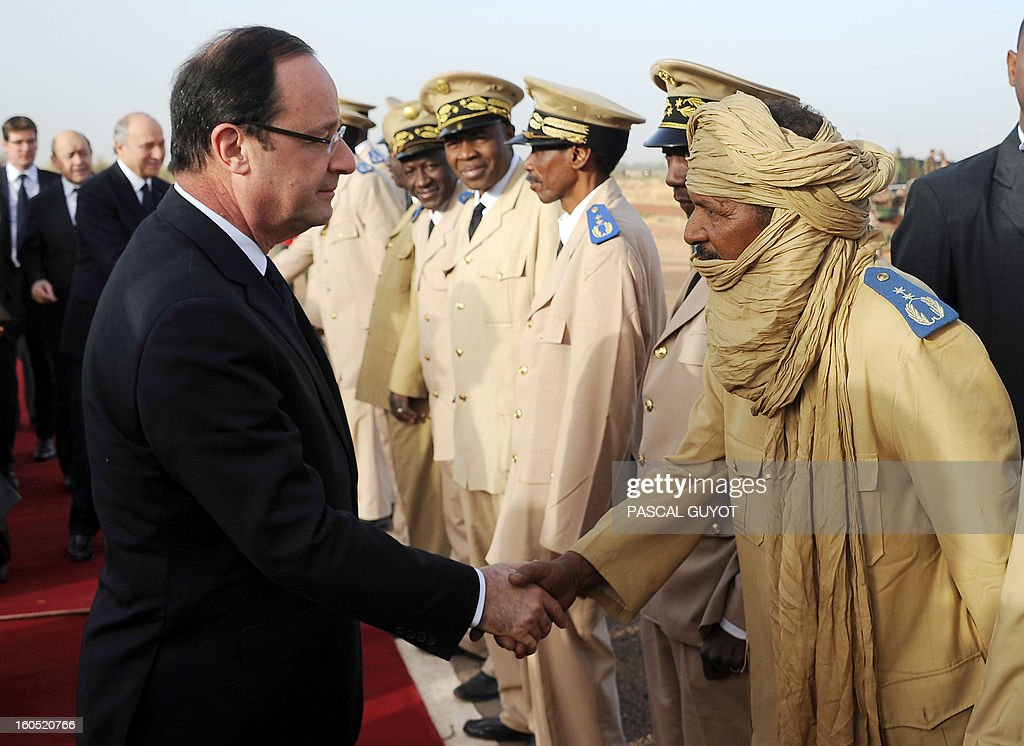 France's President Francois Hollande (L), flanked by French Foreign Affairs Minister Laurent Fabius (Back-3rdL) and French Defence Minister Jean-Yves Le Drian (Back-2ndL) shakes hands with Prefect of Mopti upon his arrival at Sevare, near Mopti, on February 2, 2013. President Francois Hollande visits Mali as French-led troops work to secure the last Islamist stronghold in the north after a lightning offensive against the extremists. Hollande will head to Timbucktu and Bamako.