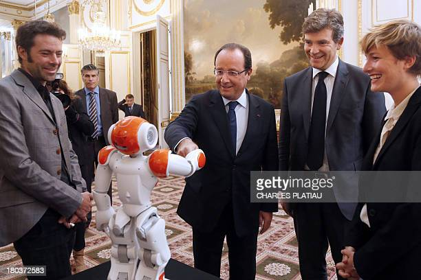 France's President Francois Hollande flanked by French Minister for Industrial Recovery Arnaud Montebourg shakes hands with an humanoid robot 'Nao'...