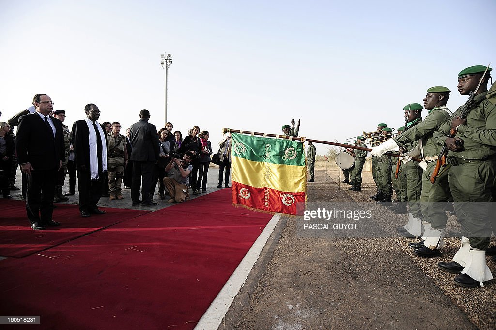 France's President Francois Hollande (L), flanked by Mali's interim president Dioncounda Traore (2ndL), is welcomed by Malian army soldiers upon his arrival at Sevare, near Mopti, on February 2, 2013. President Francois Hollande visits Mali as French-led troops work to secure the last Islamist stronghold in the north after a lightning offensive against the extremists. Hollande will head to Timbucktu and Bamako.