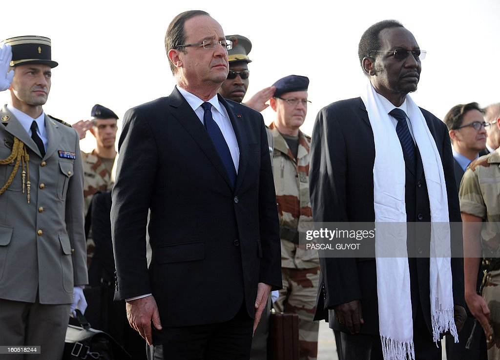 France's President Francois Hollande (2ndL), flanked by Mali's interim president Dioncounda Traore (R), is welcomed by Malian army soldiers upon his arrival at Sevare, near Mopti, on February 2, 2013. President Francois Hollande visits Mali as French-led troops work to secure the last Islamist stronghold in the north after a lightning offensive against the extremists. Hollande will head to Timbucktu and Bamako.