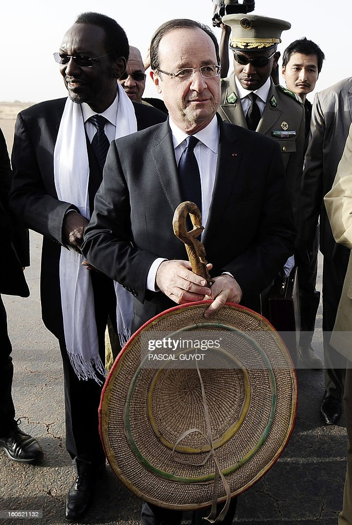 France's President Francois Hollande (C), flanked by Mali's interim president Dioncounda Traore (L), poses with the presents he received upon his arrival at Sevare, near Mopti, on February 2, 2013. President Francois Hollande visits Mali as French-led troops work to secure the last Islamist stronghold in the north after a lightning offensive against the extremists. Hollande will head to Timbucku and Bamako.