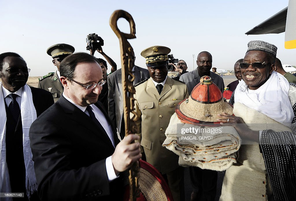 France's President Francois Hollande (2ndL), flanked by Mali's interim president Dioncounda Traore (L), receives presents upon his arrival at Sevare, near Mopti, on February 2, 2013. President Francois Hollande visits Mali as French-led troops work to secure the last Islamist stronghold in the north after a lightning offensive against the extremists. Hollande will head to Timbucku and Bamako. AFP PHOTO / PASCAL GUYOT