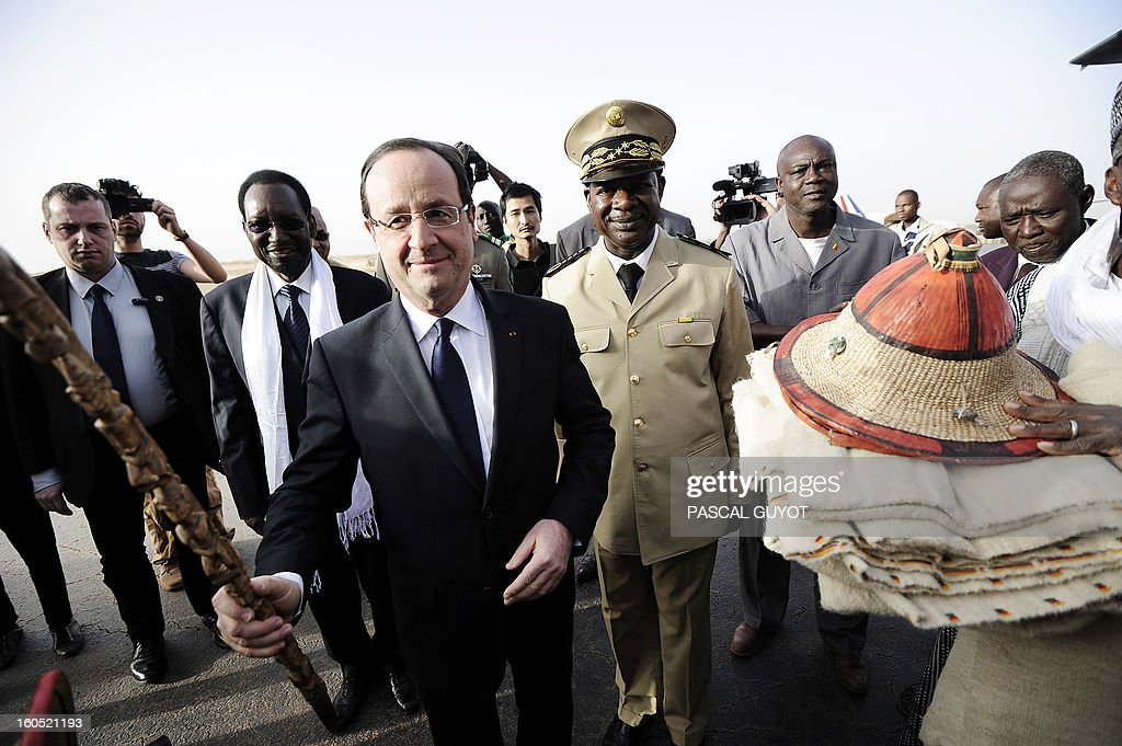 France's President Francois Hollande (C), flanked by Mali's interim president Dioncounda Traore (L), receives presents upon his arrival at the Mopti airport, in Sevare, on February 2, 2013. President Francois Hollande visits Mali as French-led troops work to secure the last Islamist stronghold in the north after a lightning offensive against the extremists. Hollande will head to Timbucku and Bamako.
