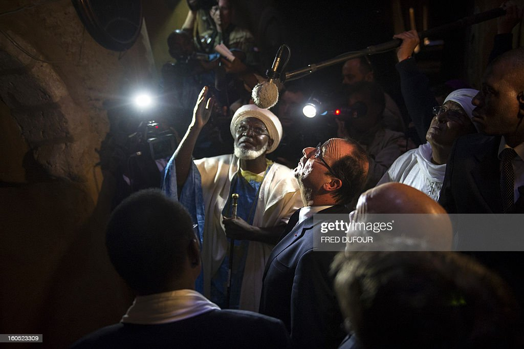 France's President Francois Hollande (C) flanked by Mali's interim president Dioncounda Traore (L), visit the Djingareyber mosque in Timbuktu, the second step of his one-day visit in Mali, on February 2, 2013. Islamists had torched the building housing priceless ancient manuscripts as they fled the town.