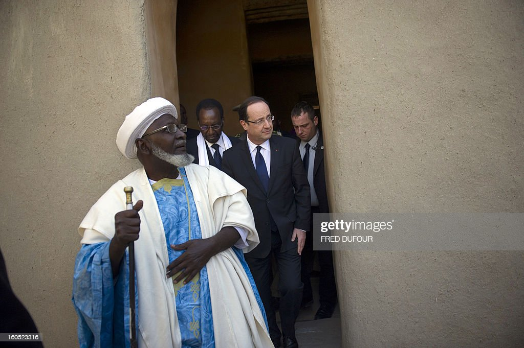 France's President Francois Hollande (C) flanked by Mali's interim president Dioncounda Traore (2ndL), visit the Djingareyber mosque in Timbuktu, the second step of his one-day visit in Mali, on February 2, 2013. Islamists had torched the building housing priceless ancient manuscripts as they fled the town.