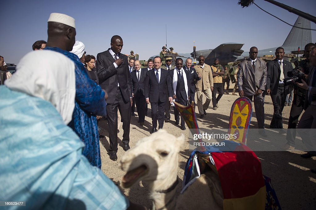 France's President Francois Hollande (C) flanked by Mali's interim president Dioncounda Traore (C-R), arrives at the airport of Timbuktu, the second step of his one-day visit in Mali, on February 2, 2013. Islamists had torched the building housing priceless ancient manuscripts as they fled the town.