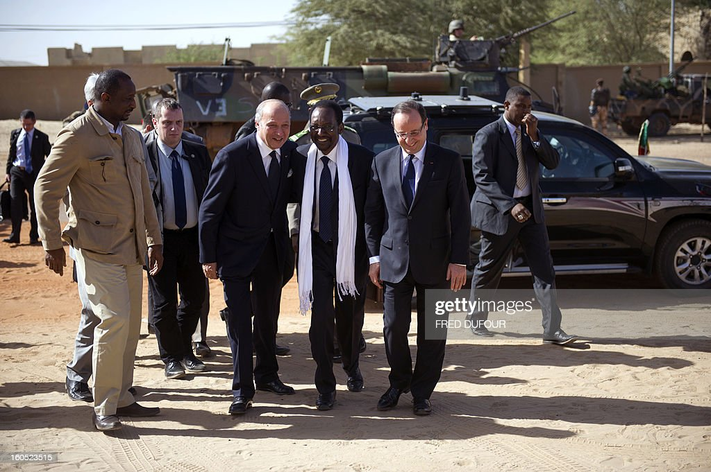 France's President Francois Hollande (2ndR) flanked by Mali's interim president Dioncounda Traore (C), and French Foreign Affairs minister Laurent Fabius arrive to visit the Djingareyber mosque in Timbuktu, the second step of his one-day visit in Mali, on February 2, 2013. Islamists had torched the building housing priceless ancient manuscripts as they fled the town.