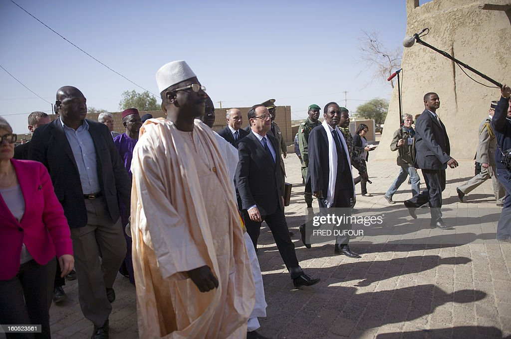 France's President Francois Hollande (C) flanked by Mali's interim president Dioncounda Traore (2ndR), and French Foreign Affairs minister Laurent Fabius (4thL) arrive to visit the Djingareyber mosque in Timbuktu, the second step of his one-day visit in Mali, on February 2, 2013. Islamists had torched the building housing priceless ancient manuscripts as they fled the town. AFP PHOTO / POOL / FRED DUFOUR