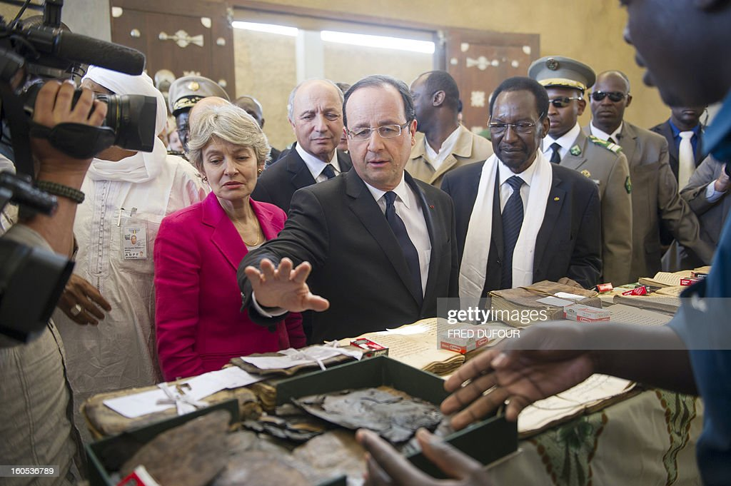 France's President Francois Hollande (C) flanked by Mali's interim president Dioncounda Traore (R) and UNESCO general director Irina Bokova of Bulgaria (L) visit the archives where documents were burnt in Timbuktu, the second step of his one-day visit in Mali, on February 2, 2013. Islamists had torched the building housing priceless ancient manuscripts as they fled the town.