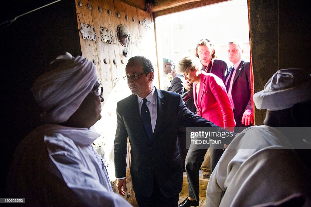 France's President Francois Hollande (C) flanked by UNESCO general director Irina Bokova from Bulgaria visits the Djingareyber mosque in Timbuktu, the second step of his one-day visit in Mali, on February 2, 2013. Islamists had torched the building housing priceless ancient manuscripts as they fled the town. AFP PHOTO / POOL / FRED DUFOUR
