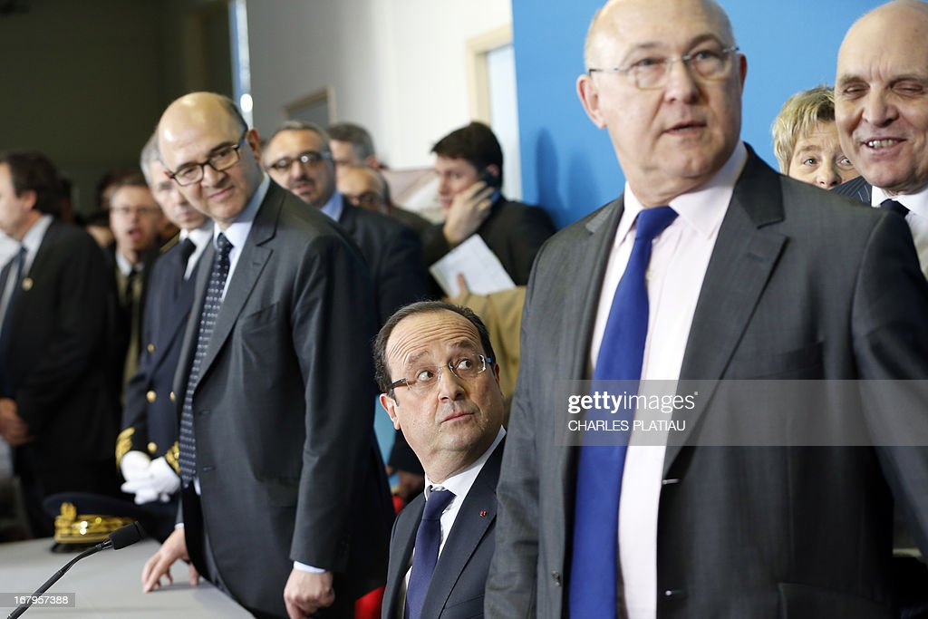 France's President Francois Hollande (C), French Economy, Finance and Foreign Trade Minister Pierre Moscovici (L) and French Labour, Employment and Social Dialogue Michel Sapin (R) take part in a meeting after visiting a leather goods maker during a one-day visit focused on employment in rural areas in Avoudrey, eastern France, on May 3, 2013. POOL