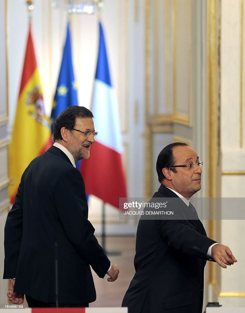 France's President Francois Hollande (R) gesture beside Spain's Prime Minister Mariano Rajoy as they leave after a joint press conference following a meeting on March 26, 2013 at the Elysee presidential Palace in Paris. AFP PHOTO / JACQUES DEMARTHON