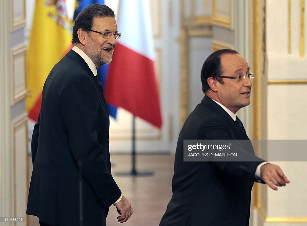 France's President Francois Hollande (R) gestures beside Spain's Prime Minister Mariano Rajoy as they leave after a joint press conference following a meeting on March 26, 2013 at the Elysee presidential Palace in Paris. AFP PHOTO / JACQUES DEMARTHON
