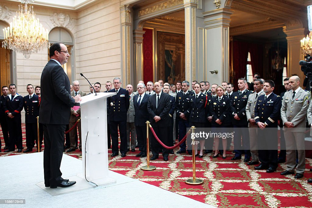 France's President Francois Hollande gives a speech during a ceremony to honor French troops home from Afghanistan at the Elysee Palace in Paris on December 21, 2012. Hollande has declared 'mission accomplished' for French combat troops who returned home recently from Afghanistan. France still has 1,500 troops in Afghanistan repatriating equipment or working in roles like providing medical care or helping run Kabul's airport. Hollande said the numbers will decline to 500 by mid-2013. Thibault Camus