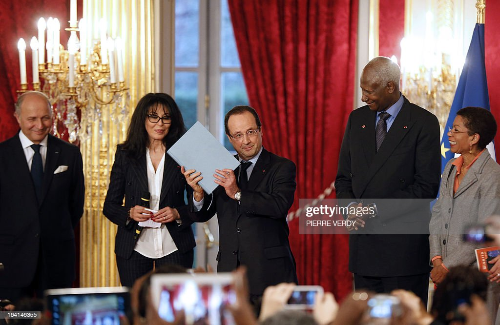 France's president Francois Hollande (C) holds a copy of the 'Blue book of the Francophone women's call' that he received from France's Junior Minister for French Living Abroad and Francophony, Yamina Benguigui (2ndL), beside General Secretary of the International Organization of Francophonie (IOF), and former Senegalese President Abdou Diouf (2ndR), following a meeting with Francophone women from the Global Forum on March 20, 2013, at the Elysee presidential Palace in Paris. The Global Forum for Francophone women gathered 400 women from 77 countries. At left is pictured French Minister of Foreign Affairs, Laurent Fabius and at right, French Junior Minister for Educational Success George Pau-Langevin.