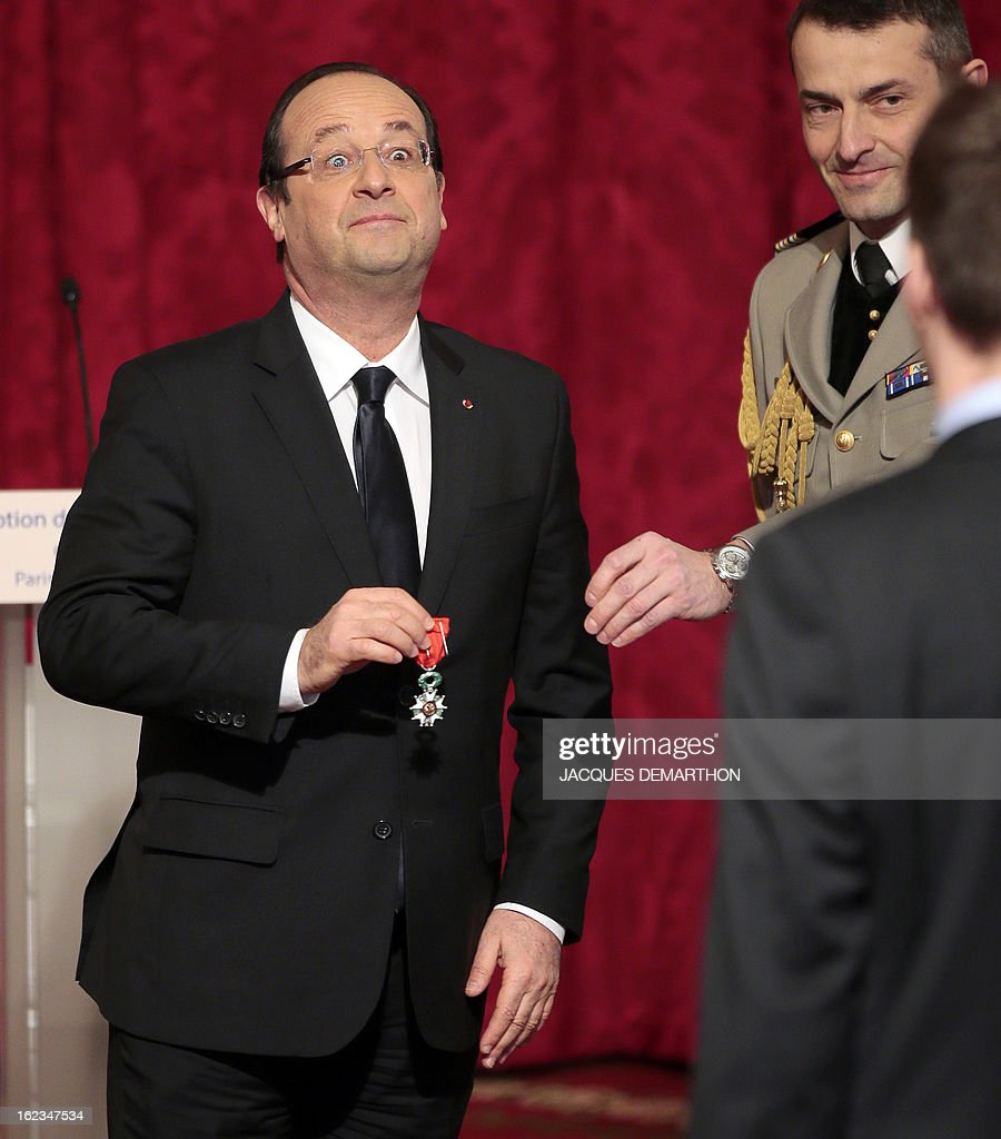 France's President Francois Hollande (L) holds the Legion of Honor decoration before awarding French swimmer and 2012 London Paralympic Games gold medalist Charles Rozoy during a ceremony at the Elysee Palace on February 22, 2013 in Paris. AFP PHOTO / POOL / JACQUES DEMARTHON
