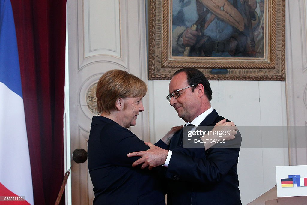 France's President Francois Hollande (L) hugs German Chancellor Angela Merkel (R), at the end of a speech at the Verdun's town-hall, northeastern France, on May 29, 2016, during a remembrance ceremony to mark the centenary of the battle of Verdun. The battle of Verdun, in 1916, was one of the bloodiest episodes of World War I. The offensive which lasted 300 days claimed more than 300,000 lives. / AFP / POOL / Thibault Camus