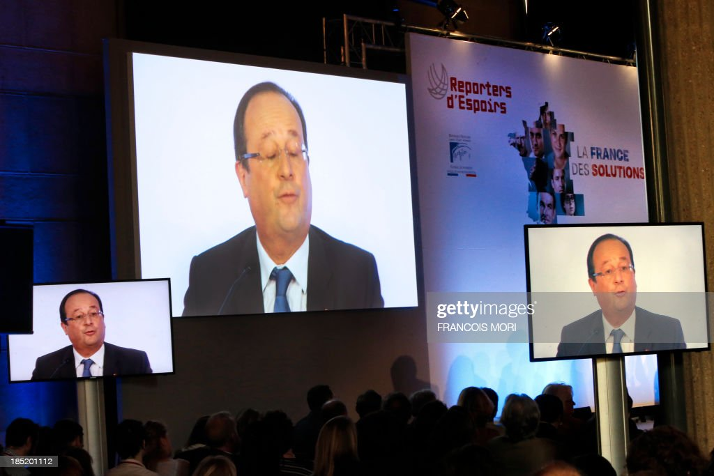 France's President Francois Hollande is displayed on screens as he delivers a speech at a meeting called 'Solutions for France' and organized by Reporters d'Espoir (Reporters of Hopes) at Iena Palace in Paris, on October 18, 2013. The meeting aimed at promoting French innovative and successful companies in sectors such as tourism, environment, agriculture or handicap where France can have a leadership.