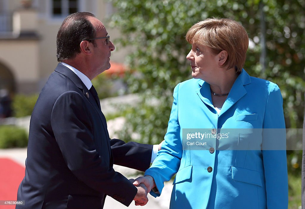 France's President Francois Hollande is greeted by Germany's Chancellor Angela Merkel upon his arrival at Schloss Elmau for the summit of the G7...