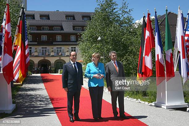 France's President Francois Hollande is greeted by Germany's Chancellor Angela Merkel and her husband Joachim Sauer upon his arrival at Schloss Elmau...