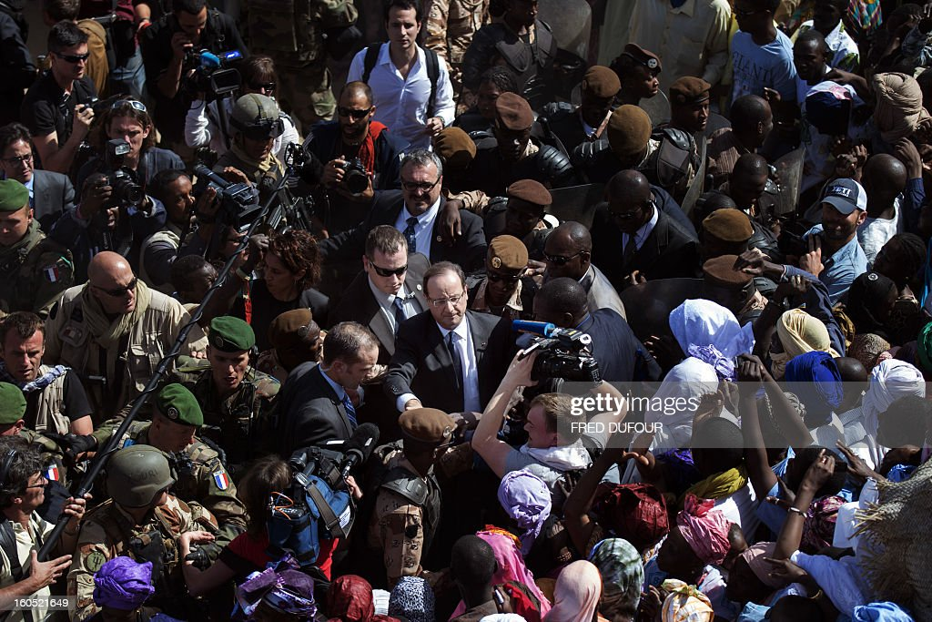France's President Francois Hollande (C) is welcomed by Malian people as he arrives at Timbuktu, the second step of his one-day visit in Mali, on February 2, 2013. Hollande visits Mali as French-led troops work to secure the last Islamist stronghold in the north after a lightning offensive against the extremists. AFP PHOTO FRED DUFOUR / AFP / FRED DUFOUR