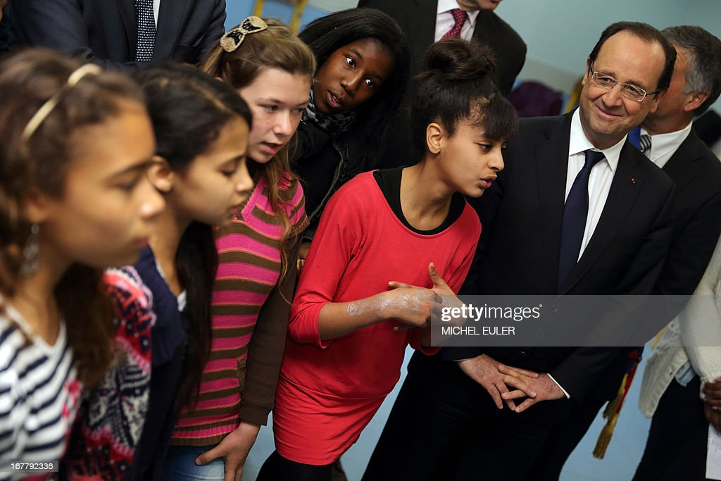 France's President Francois Hollande (R) listens to pupils performing music and songs in a school during a visit focused on the youth employment on April 30, 2013 in Les Mureaux, a Paris' suburb.