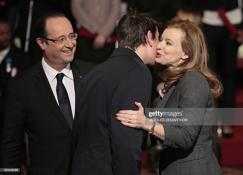 France's President Francois Hollande (L) looks at his companion Valerie Trierweiler (R) who congratulates French athlete Pascal Pereira-Leal, table tennis bronzer medalist in the 2012 London Paralympic Games, after awarding him in the Order of Merit, during an awarding ceremony at the Elysee presidential Palace on February 22, 2013 in Paris. AFP PHOTO / POOL / JACQUES DEMARTHON