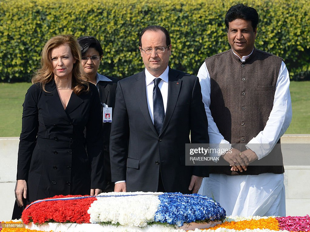 France's President Francois Hollande (2R) poses for a photo after laying a wreath with his partner Valerie Trierweiler (L) at a ceremony at Rajghat, the memorial of India's founding father Mahatma Gandhi in New Delhi on February 14, 2013. French President Francois Hollande embarked on a fresh push to clinch a USD 12-billion sale of Rafale fighter jets as he held talks in India on his first visit to Asia since taking office. The Socialist president was accompanied by a high-powered delegation of five ministers including Foreign Minister Laurent Fabius and Defence Minister Jean-Yves Le Drian and the chiefs of more than 60 top French companies.