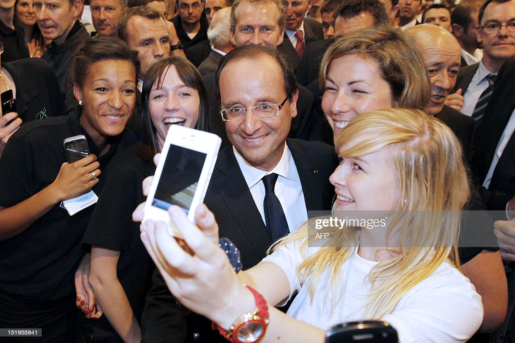 France's President Francois Hollande (C) poses for a photo as he attends the International breeding fair (Space) on September 11, 2012 in Rennes, western France.