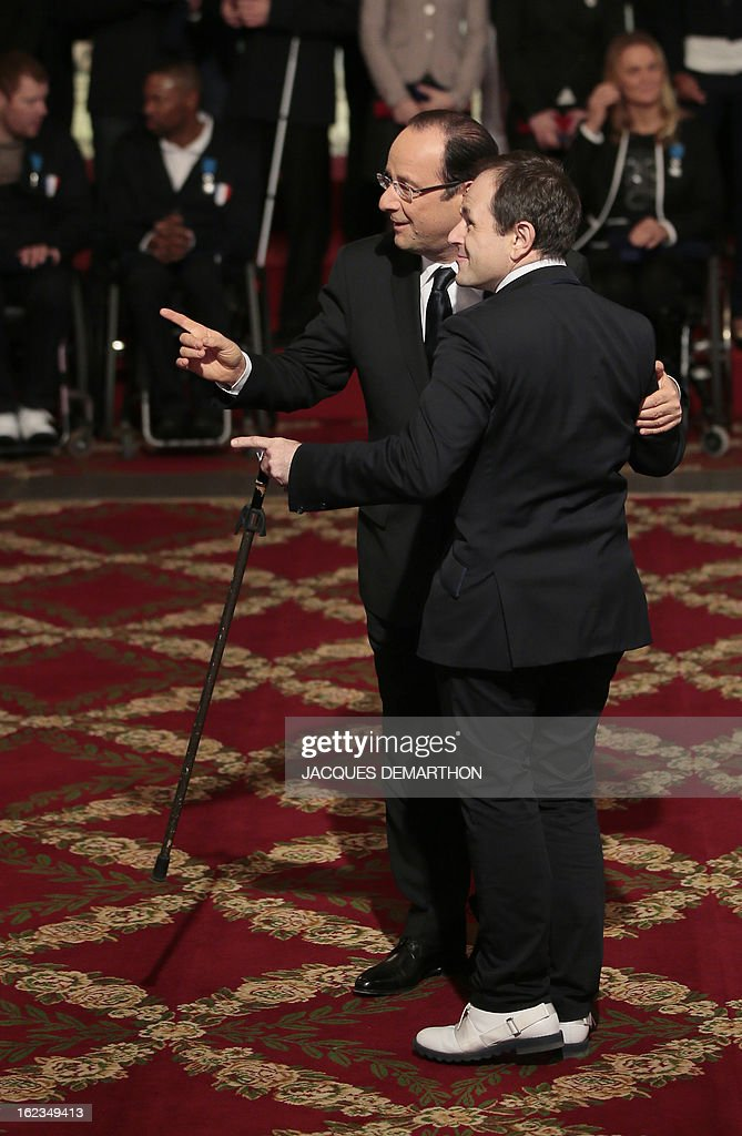 France's President Francois Hollande (L) poses for a picture with French fencer Damien Tokatlian, silver medalist in the 2012 London Paralympic Games, after awarding him in the Order of Merit during an awarding ceremony at the Elysee presidential Palace on February 22, 2013 in Paris.