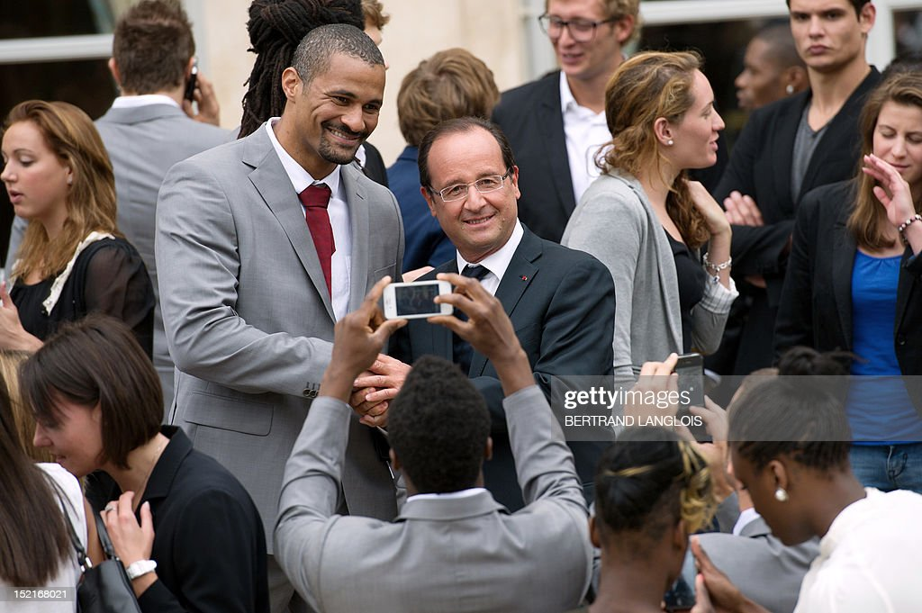 France's President Francois Hollande (C) poses for pictures with French Gold medalist handball athlete Didier Dinart (C,L) among French athletes, following London 2012 Olympic and Paralympic Games, on September 17, 2012, after a ceremony at the Elysee Palace in Paris.