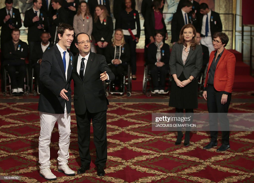 France's President Francois Hollande poses with French athlete Pascal Pereira-Leal, table tennis bronzer medalist in the 2012 London Paralympic Games, after awarding him Knight in the Order of Merit, as his companion Valerie Trierweiler (2ndR) and Sports Minister Valerie Fourneyron (R) look on during an awarding ceremony at the Elysee presidential Palace on February 22, 2013 in Paris. AFP PHOTO / POOL / JACQUES DEMARTHON
