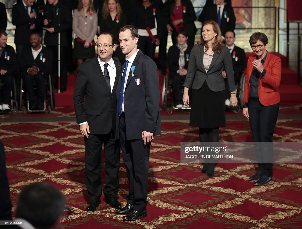 France's President Francois Hollande (L) poses with French athlete Romain Noble, silver medalist in the 2012 London Paralympic Games after awarding him in the Order of Merit as his companion Valerie Trierweiler (2ndR) and Sports Minister Valerie Fourneyron (R) look on during an awarding ceremony at the Elysee presidential Palace on February 22, 2013 in Paris. AFP PHOTO / POOL / JACQUES DEMARTHON