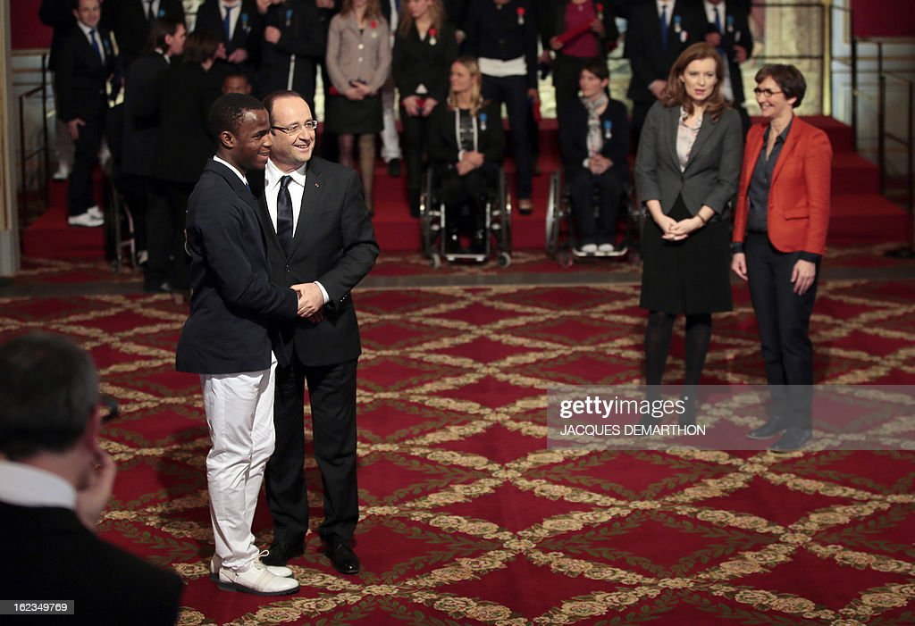 France's President Francois Hollande (2ndL) poses with French sighted football player Yvan Wouandji-Kepmegni (L), silver medalist in the 2012 London Paralympic Games, after awarding him Knight in the Order of Merit, as his companion Valerie Trierweiler (2ndR) and Sports Minister Valerie Fourneyron (R) look on during an awarding ceremony at the Elysee presidential Palace on February 22, 2013 in Paris. AFP PHOTO / POOL / JACQUES DEMARTHON