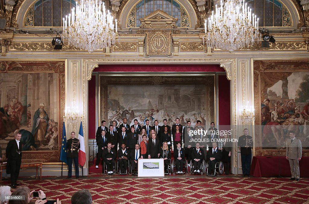 France's President Francois Hollande (C) poses with paralympic athletes during an awards ceremony at the Elysee Palace on February 22, 2013 in Paris.
